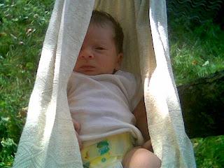 Szöveg: ugyanaz a kendő, immár lengőágyként használva. Kép: a fenti kendő kifeszítve, megkötve, és beléhelyezve a baba. A baba rövidujjúban van, eldobható pelusban és csak a fél szeme látszik, az is félig csukva. Vagy inkább nyitva.