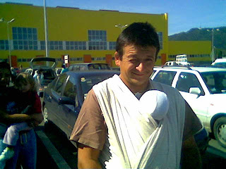 Szöveg: Nemcsak mamagolni, de apagolni is jó :) Kép: egy nagy bevásárlóközpont előtti parkolóban apuka hasára kötve egy baba. Apuka hunyorít a kamerába.