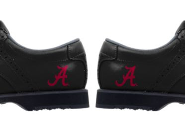Black heels of U of Alabama golf shoes with the red letter A in cursive as a logo on the back part of the shoes near the soles.