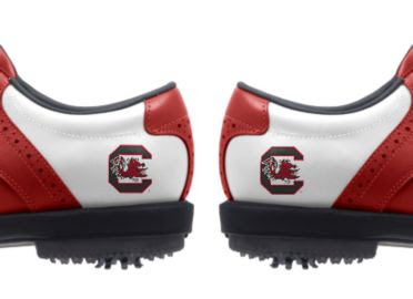 University of South Carolina golf shoes that are white with red trim and have college logos on the sides with a Gamecock logo above plastic cleats.
