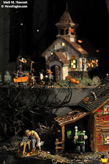 a farmer prepares to slaughter animals near a barn in the an ax to grind halloween village decoration at bronners