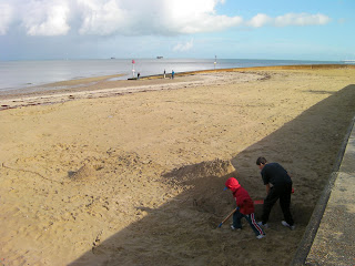 excavating sand. digging a hole in the beach