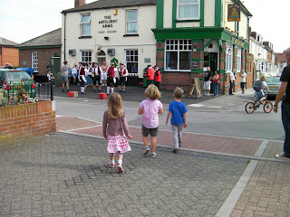 Morris men performing outside pub. they need beer too