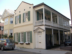 A typical Charleston home with earthquake rods, a single door to the side porches and a garden.