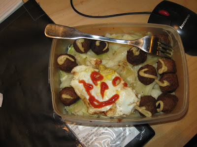 Köttbullar med stekt vitkål och ett stekt ägg.