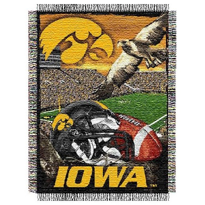 Iowa Hawkeyes football blanket with Kinnick Stadium in the background and a black football helmet in the foreground.