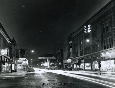 From the Ohio Historical Society: Night scene on Court Street in Athens, Ohio, ca. 1950-1959. Restaurants, stores, theaters and other businesses catering to Ohio University students can be seen. The banner hanging across the street reads, 'Vote for Bill 'Tiny' Blackman for Senior Class President.'