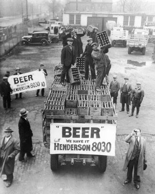 Men atop beer delivery truck (w. sign reading BEER-WE HAVE IT-CALL HENDERSON 8030) hoist cases of beer triumphantly while man standing in front of truck drinks out of beer bottle following the repeal of Prohibition.