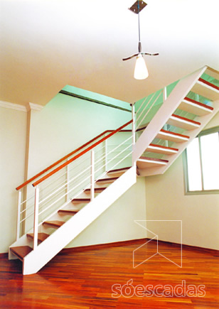 Escada em L com degraus revestidos em madeira.