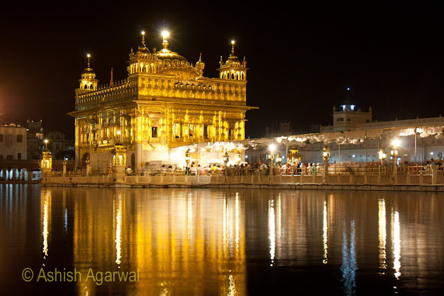The Harmandir Sahib in Amritsar at night, with lights reflecting in the holy sarovar surrounding it