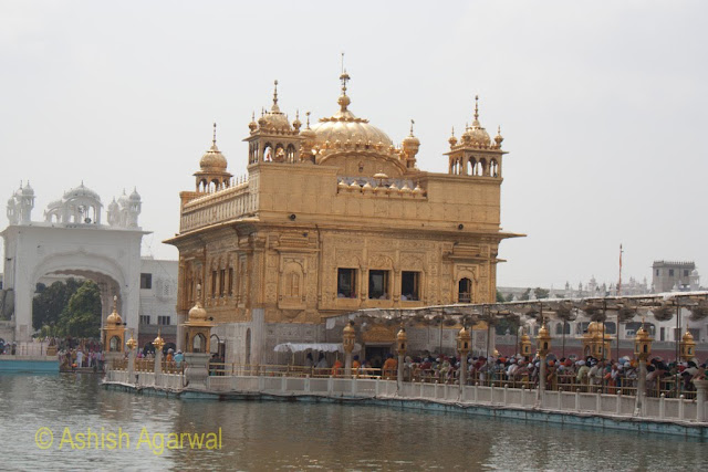 View of the Darbar Sahib along with the causeway in the middle of the sarovar, with devotees thronging the causeway in the Golden Temple in Amritsar