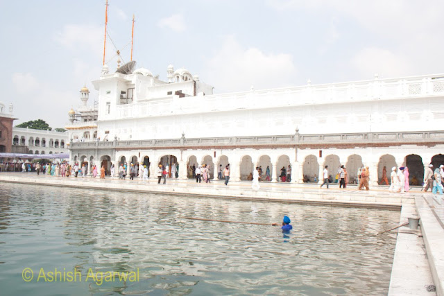 View of volunteer cleaning the sarovar of the Golden Temple while devotees pass by