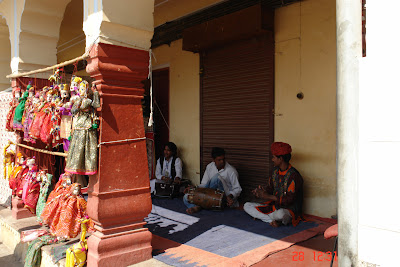 Dolls in front of some musicians playing traditional music in Jaipur, Rajasthan, India