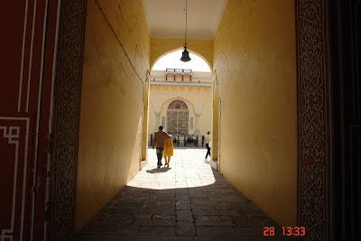 Photo: A couple walking through an arched doorway at the Jaipur City Palace