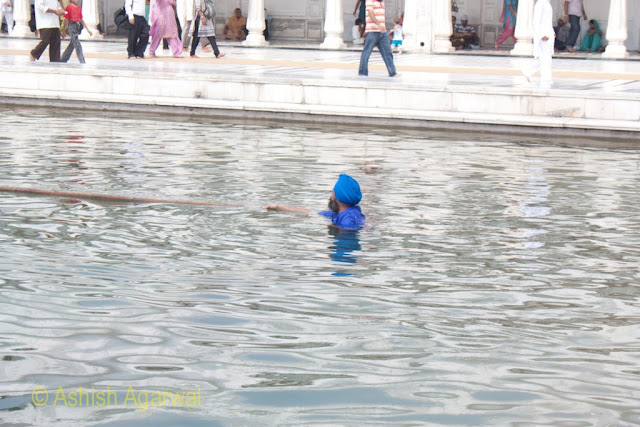 A Sikh volunteer inside the sarovar of the Golden Temple in Amritsar