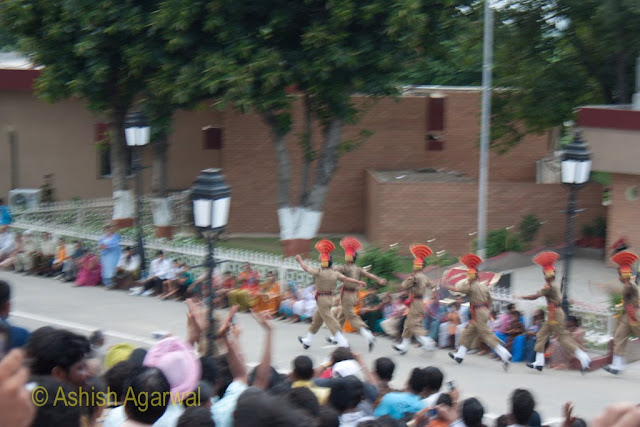 Slightly blurred image of Border Security Force personnel marching towards the Wagah border