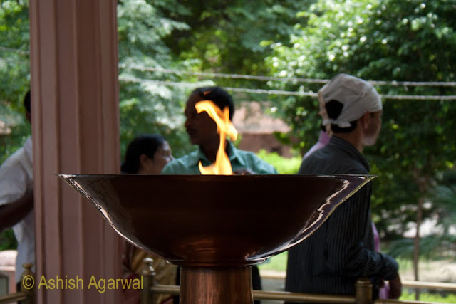 The ceremonial flame at the Jallianwala Bagh at Amritsar with people in the background