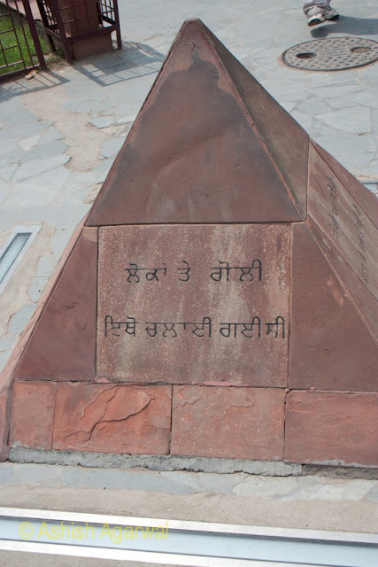 Close up of the Gurmukhi script on the stone in the Jallianwala Bagh Garden in Amritsar from where soldiers fired