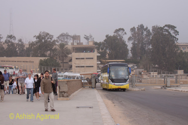 Cairo Pyramids - A bus full of tourists arriving at the entrance to the pyramids in Giza