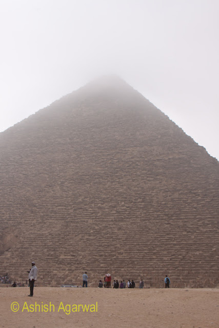Cairo Pyramids - Tourists in front of the Great Pyramid of Cheops, with fog at the top