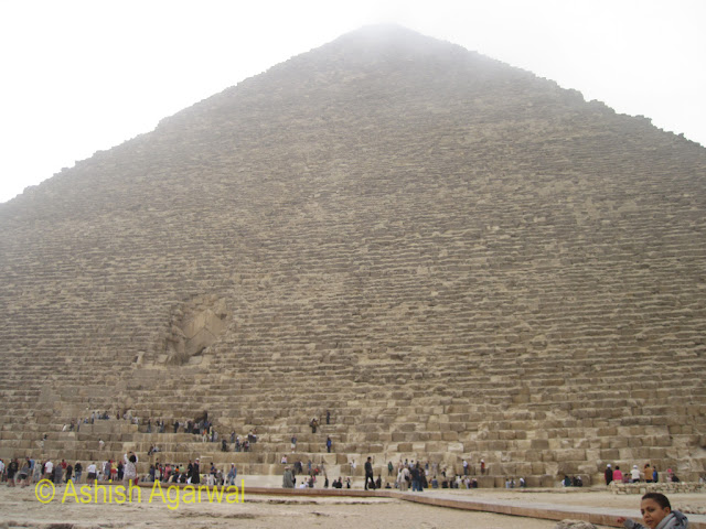 Cairo Pyramids - Almost the full size of the pyramid along with people at the base of the Pyramid