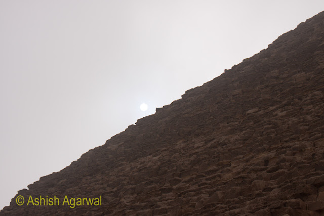 Great Pyramid of Giza - The sun peeking from behind the stone structure of the Pyramid