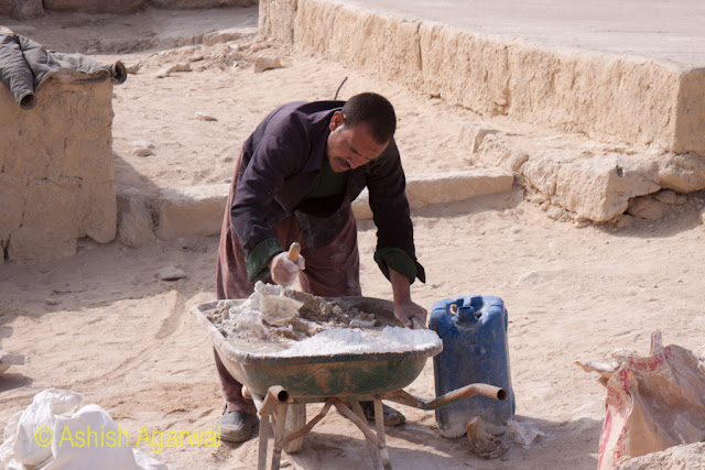 Cairo Pyramids - Worker mixing the concrete setting liquid next to the Great Pyramid of Giza