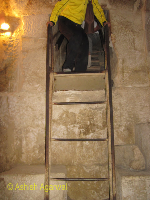 Cairo Pyramids - Tourist preparing to climb down the ladder leading to the burial chamber, in the structure next to the Great Pyramid