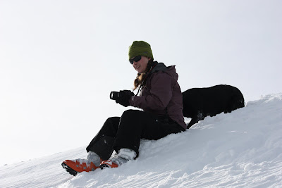I am sitting on a snow covered hill wearing a green hat, sunglasses, dusky purple jacket, black ski pants, and my orange AT ski boots.  I am holding my camera while smiling and looking down the hill as a black lab sits behind me on the slope.