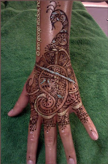 gilded henna tattoo back of hand peacock pattern
