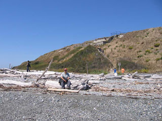 Josh sitting on a driftwood log on the beach at Fort Casey