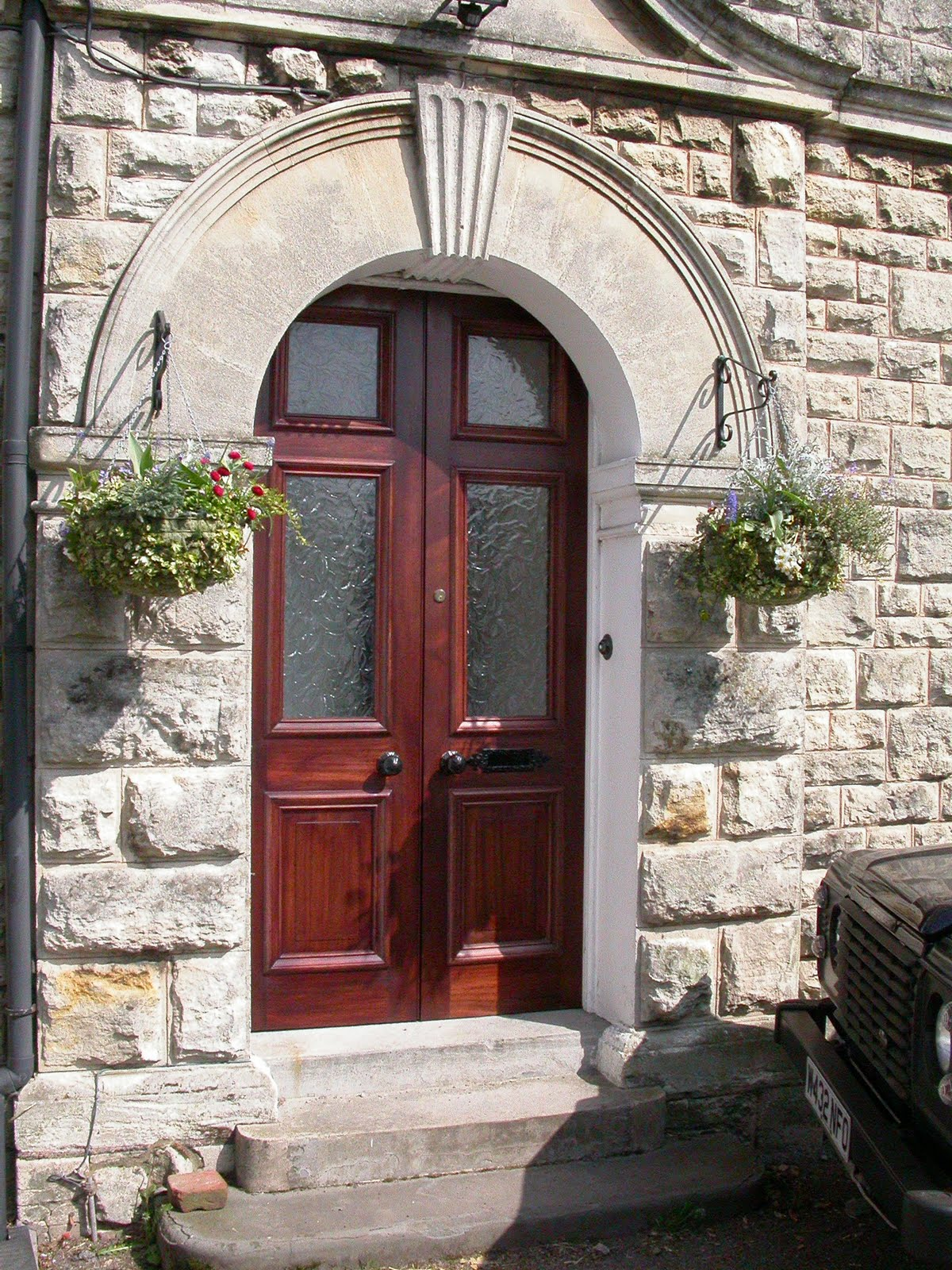 Hard wood front doors with raised panels, moulding and opaque glass.
