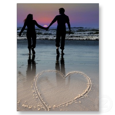 Boy and girl child holding hands on. Two people walking on beach holding.