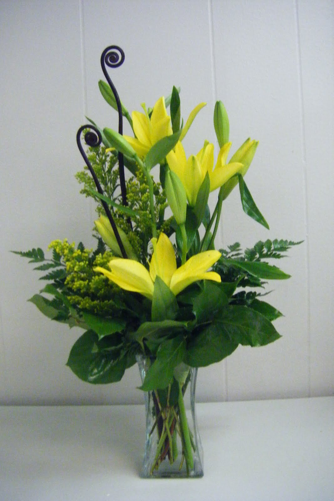 Freds flowers funky monkey a simplistic arrangement of lilies and monkey tails in a square flare vase 30 reviewsmspy