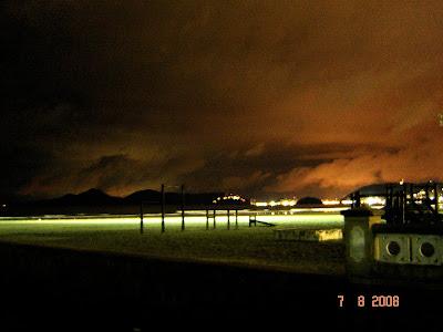 Foto noturna da praia de Santos tendo ao fundo a Ilha Porchat iluminada e a ilha Urubuqueçaba - Foto de EMILIO PECHINI em 07/08/2008