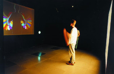 Image of a member of the public interacting in Videoplace with his on-screen image.
