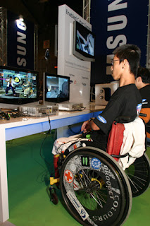Enabled Cyber Gamers - Samsung and Society for Disabled - Singapore. Image of an enabled gamer playing an Xbox game with an adapted controller.