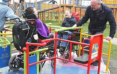 Image of an accessible round-a-bout, with two young lads in wheelchairs being spun round by their Dads, all grinning broadly.