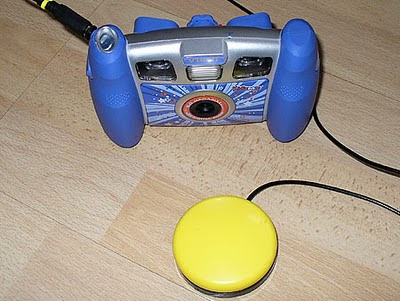Image of a Switch adapted VTech Kidizoom digital camera with connected yellow accessibility switch.