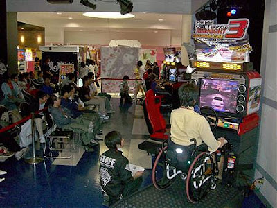 Image of a Namco/Wangan Midnight Maximum Tune 3 arcade racing game - with the seat removed and replaced with a wheelchair ramp. It seems the foot pedals have been replaced by a hand control.