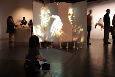 Image of a young child pressing a blue illuminated switch to affect a video art installation.
