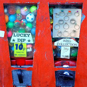 Image of a capsule toy vending machine stating 'Lucky Dip - 10p' next to a toy ring vending machine. Both looking a bit tatty.