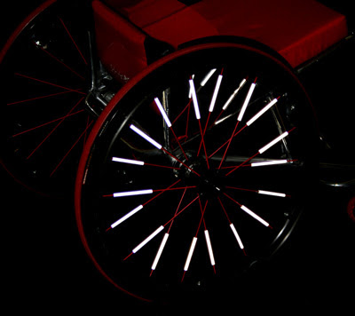 Image of a wheelchair wheel covered in thin white reflectors.