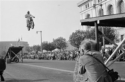 Image of Evel Knievel jumping between two ramps on a motorbike in the 1960's.