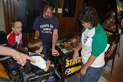 Image of two lads being given instructions on how to play a switch adapted pinball machine, using a huge mirror to make it easier to view the action from wheelchair height. Taken at Assistive Technology Partners' AbleGames 2009