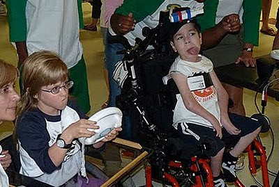 Two young children playing a Wii Mario Kart. One using a standard steering wheel, the other using a cap mounted controller, enabling alternative access to the game.