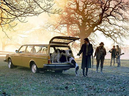 I've got a Volvo by the way! Not this one though. Image of an old yellow brick estate Volvo with some toffs in the background with shot-guns. The boot is open, with a couple of dogs jumping out.