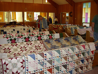 church pews with quilts over the backs