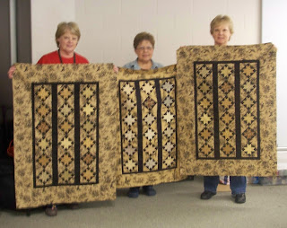 Jeanne, Theresa and Connie holding our Jo Morton toile quilt tops