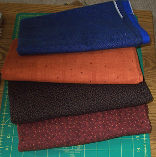 red, black, orange & blue fabrics for mystery quilt